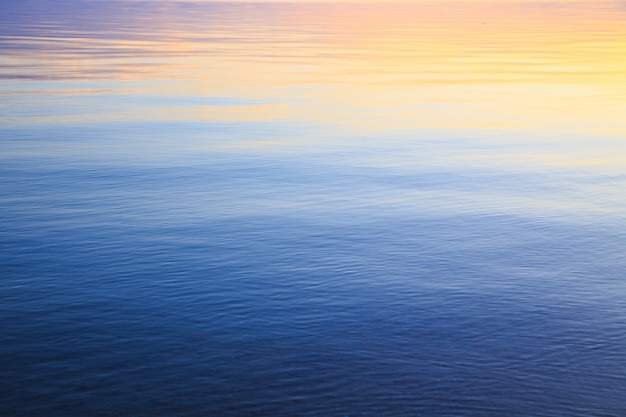 Texture of clear sea or ocean water in blue and orange colors