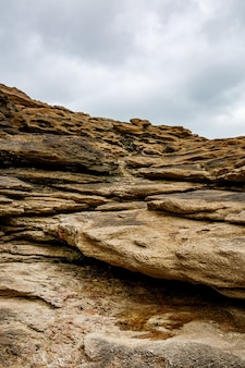 Texture of coastal old stone. rock wallpaper. cloudy sky