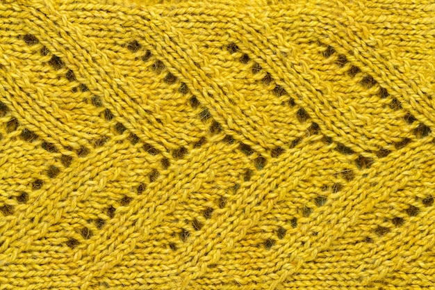 The texture of a color of mustard knitted yarn. knitted and winter clothes