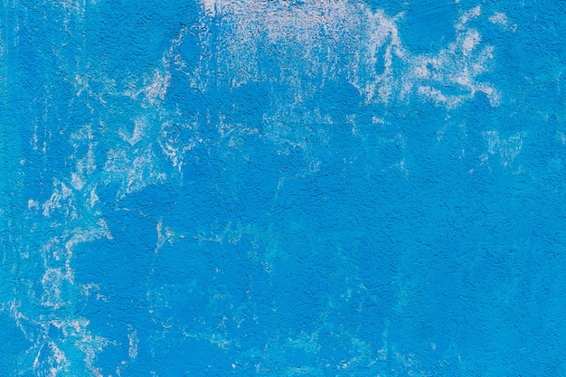 The texture of the concrete cement wall painted in blue color with white splashes. background for wallpapers