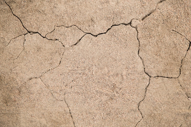 The texture of the crack in the ground with sand in the form of lightning close-up. background cracked earth