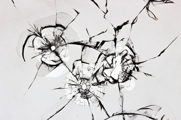Texture of cracked broken glass on a white surface