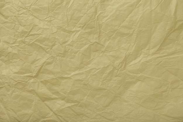 Texture of crumpled beige wrapping paper, closeup. golden old background
