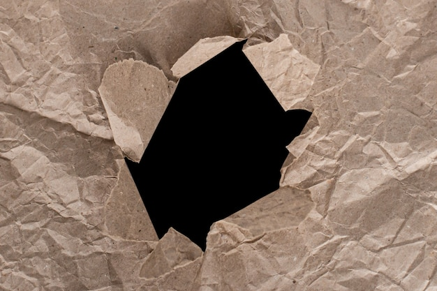 The texture of crumpled craft paper with a hole