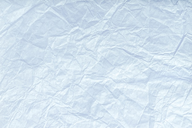 Texture of crumpled light blue wrapping paper, closeup. white old background.