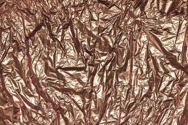 Texture of crumpled sheet of bronze foil, background closeup.