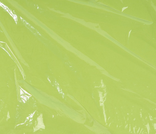 Texture of crumpled transparent polyethylene on a green surface, full frame