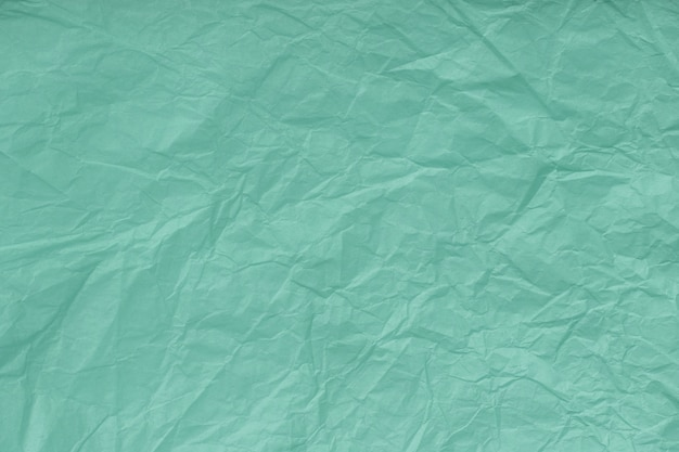 Texture of crumpled turquoise, wrapping paper, closeup. green old