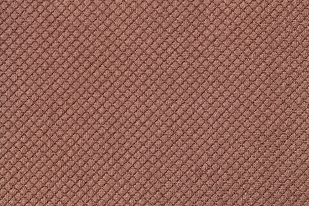 Texture of dark brown fluffy fabric background with rhomboid pattern, macro.