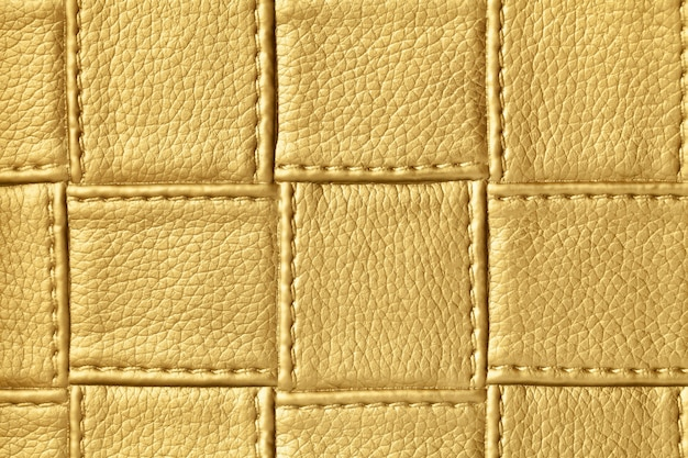 Texture of dark golden and yellow leather with square pattern and stitch, macro.