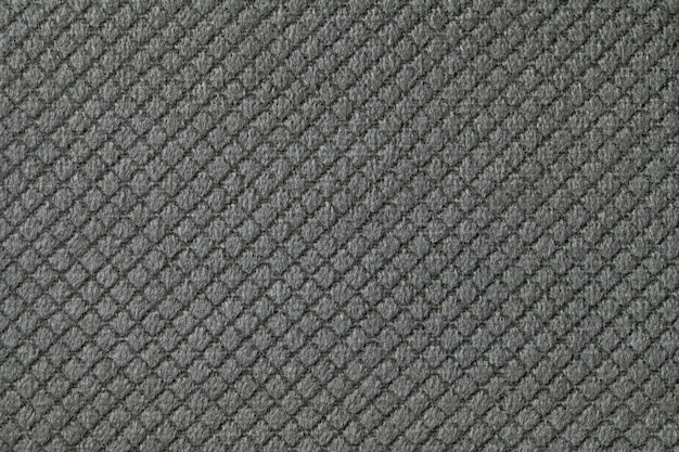 Texture of dark gray fluffy fabric background with rhomboid pattern, macro. abstract backdrop from decorative black woven textile material.