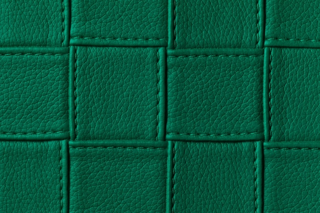 Texture of dark green leather background with square pattern and stitch.