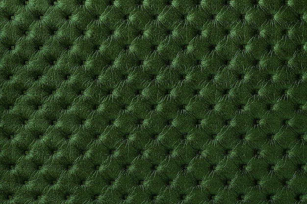 Texture of dark green leather fabric background with capitone pattern. textile with chesterfield style.