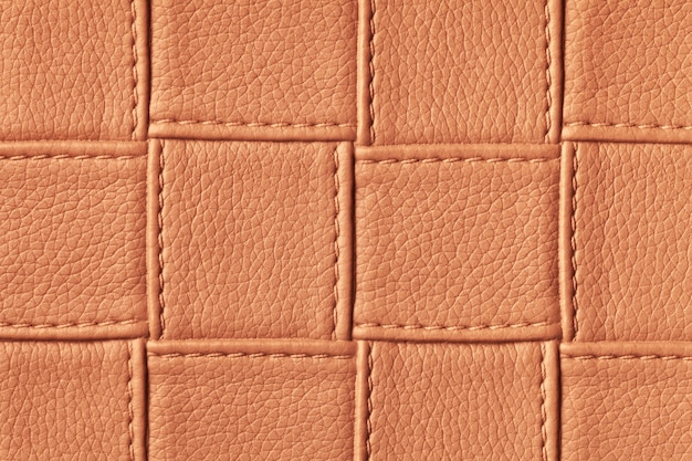 Texture of dark orange and red leather background with square pattern and stitch