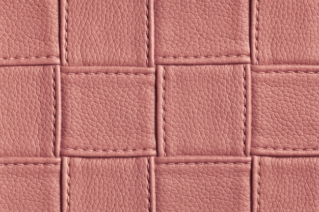 Texture of dark pink and rose leather background with square pattern and stitch