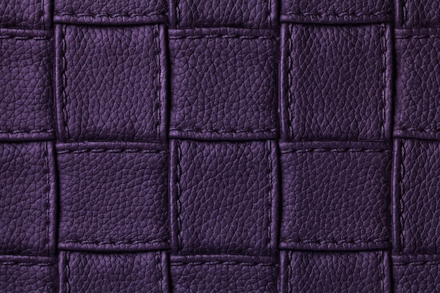 Texture of dark purple leather background with square design and stitch, macro.