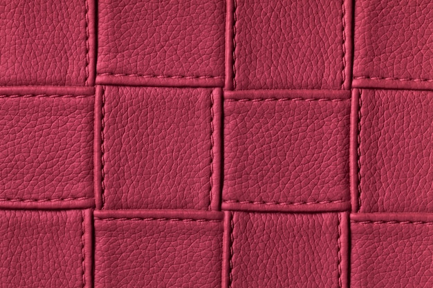 Texture of dark purple leather background with square pattern and stitch.