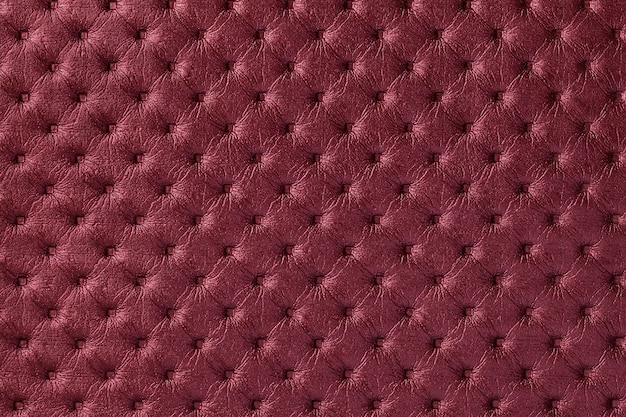 Texture of dark red leather fabric background with capitone pattern, macro. wine textile of retro chesterfield style.