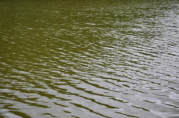 The texture of dark river water under the influence of wind, imprinted in perspective. horizontal image