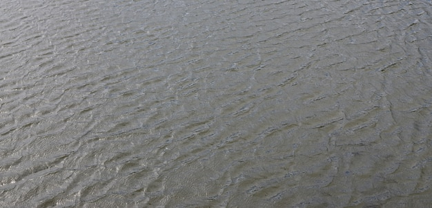 The texture of dark river water under the influence of wind, imprinted in perspective.