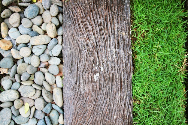 Texture detail of gaden design with white gravel, old wood and grass decoration on the ground in garden.
