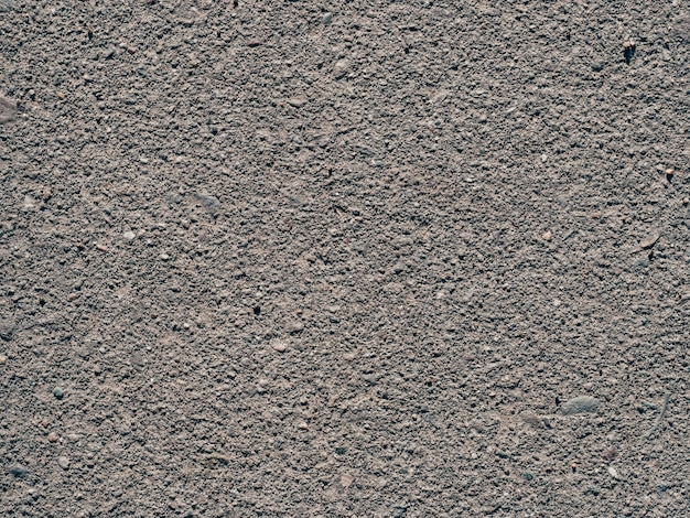Texture of dirty old asphalt with stones close-up