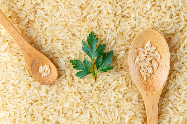 Texture of dry golden yellow long rice with wooden spoons and fresh green parsley