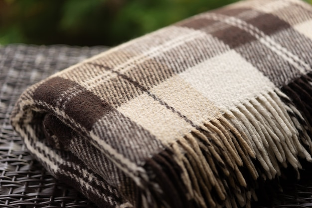 The texture of the fabric of a warm woolen brown beige checkered plaid with fringes.