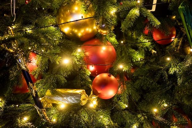 ライトと装飾と溶岩の赤いボールとテクスチャモミの枝。新年とクリスマスツリーの断片。クローズアップ、ソフトフォーカス、背景をぼかす