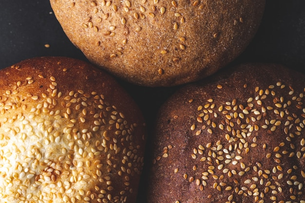 Texture of fresh yellow and brown sesame buns close up. top view. flour and bakery products. bread
