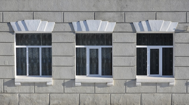 Texture of a glazed modern windows of a grey concrete building