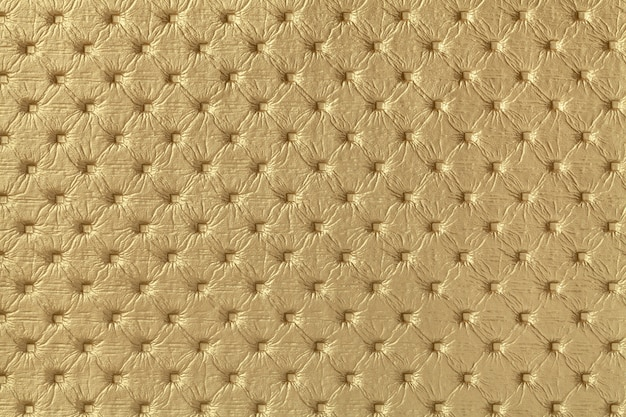Texture of golden leather fabric background with capitone pattern. yellow textile of retro chesterfield style.