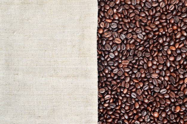 Texture of a gray canvas made of old and coarse burlap with coffee beans on it