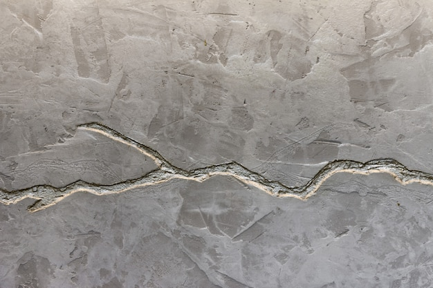 The texture of the gray concrete wall is decorated with a deep crack of silver color.