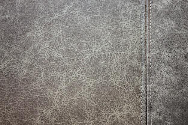 Текстура серая кожа с вертикальным декоративным швом, фон крупным планом