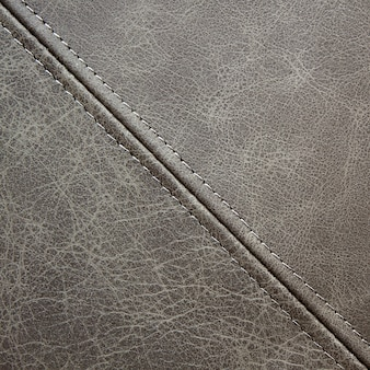 Texture gray leather with a diagonal decorative seam, closeup background