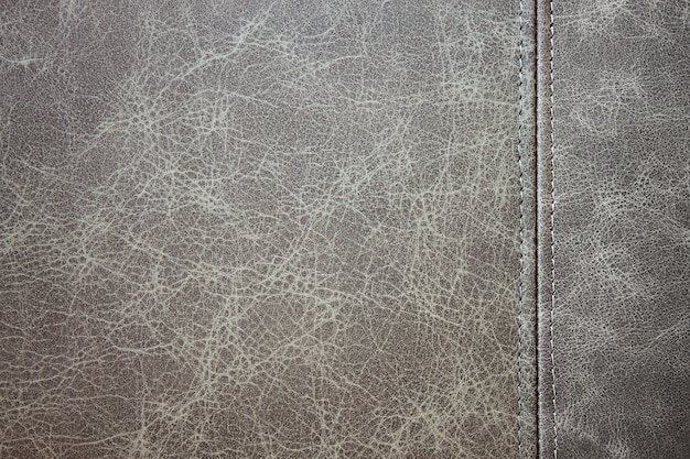 Texture gray leather with a vertical decorative seam, closeup background