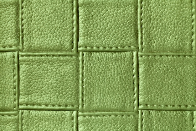 Texture of green leather surface with square pattern and stitch