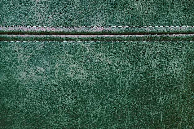 水平方向の装飾的な縫い目、クローズアップの背景を持つテクスチャグリーンレザー