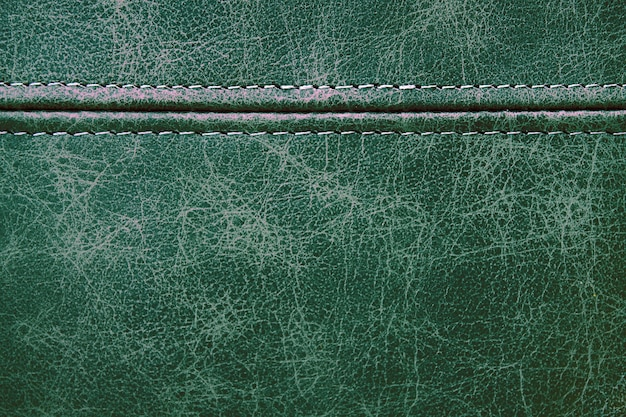 Texture green leather with a horizontal decorative seam, closeup background