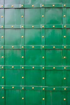 Texture of green old metal door with rivets