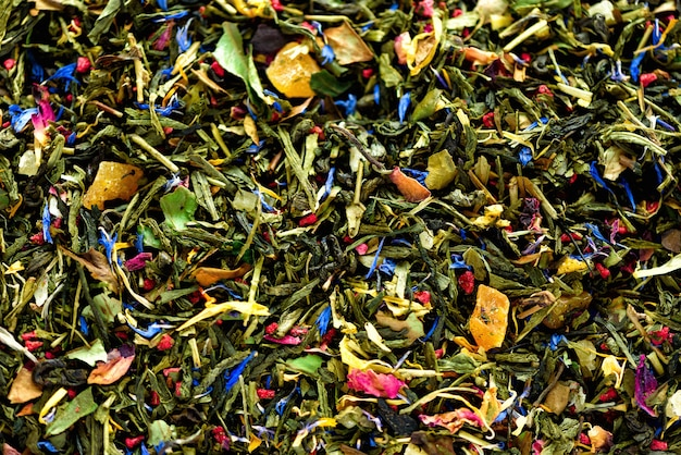 Texture of green tea with dried petals of blue flowers, calendula, cornflower. food. organic healthy herbal leaves, detox tea.