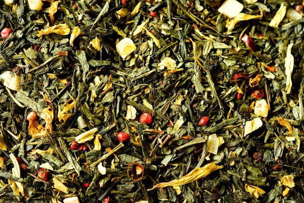 Texture of green tea with dried petals yellow flowers and red pepper. food. organic healthy herbal leaves, detox tea.
