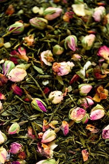 Texture of green tea with rose petals. dried rosebuds texture closeup. food. organic healthy herbal leaves, detox tea.