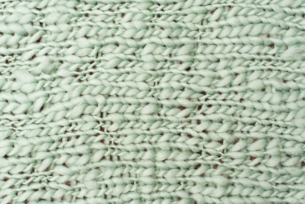 Texture of green wool big knit blanket. large knitting. plaid merino. top view