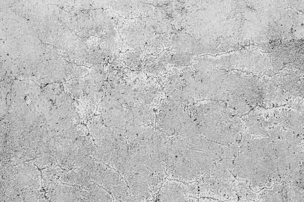 Texture of a grey concrete wall with curly cracks