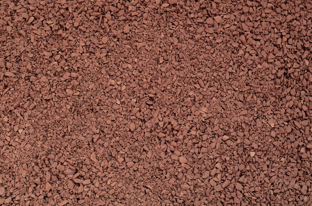 Texture of ground coffee in the form of many small pebbles of dark brown color