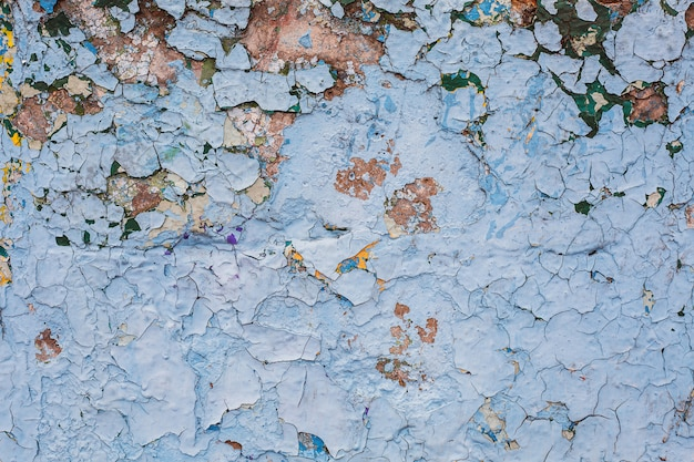 Texture grunge background of concrete stone wall with peeling paint of blue color