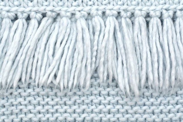 The texture of knitted wool fabric of purl loops with fringe.