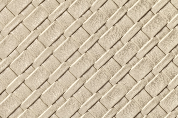 Texture of light beige and sand leather background with wicker pattern